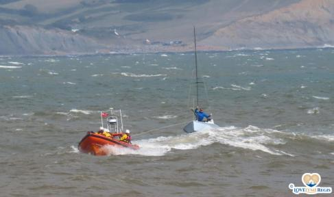 Lifeboat rescue towing a sailing boat in rough seas